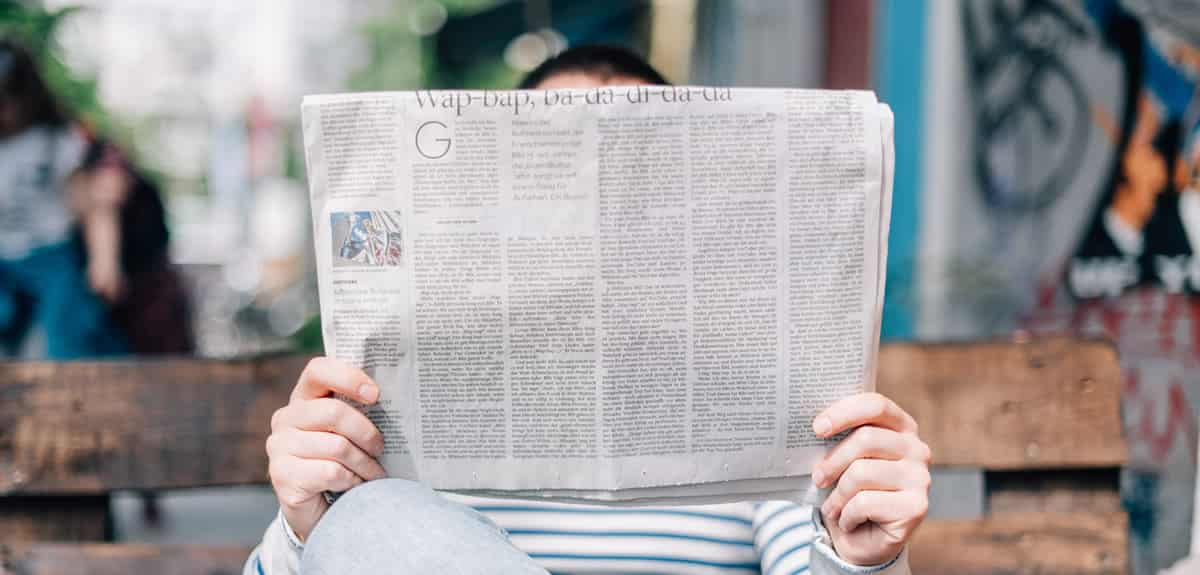An image of a man reading a newspaper whilst sitting on a bench.
